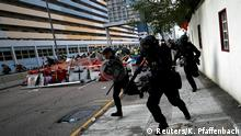 Riot police walk past a barricade as they clash with demonstrators during a protest in Hong Kong, China, August 24, 2019. REUTERS/Kai Pfaffenbach