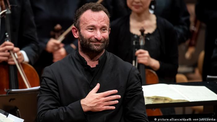 Kirill Petrenko with orchestra members seen in background