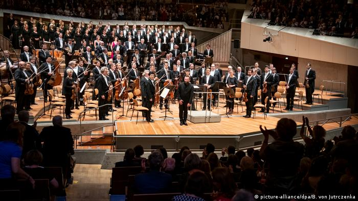Orchestra members, choristers and conductor onstage in the Berlin Philharmonie