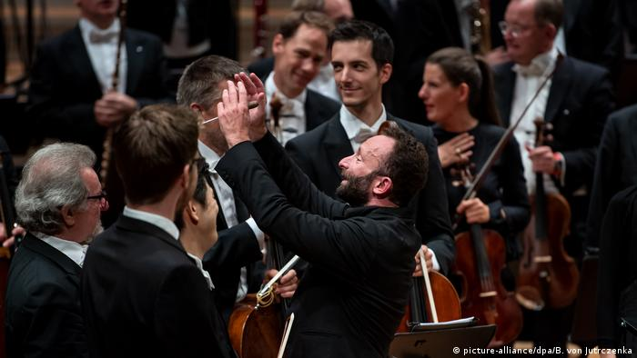 Conductor applauds musicians and directs them to stand up (picture-alliance/dpa/B. von Jutrczenka)