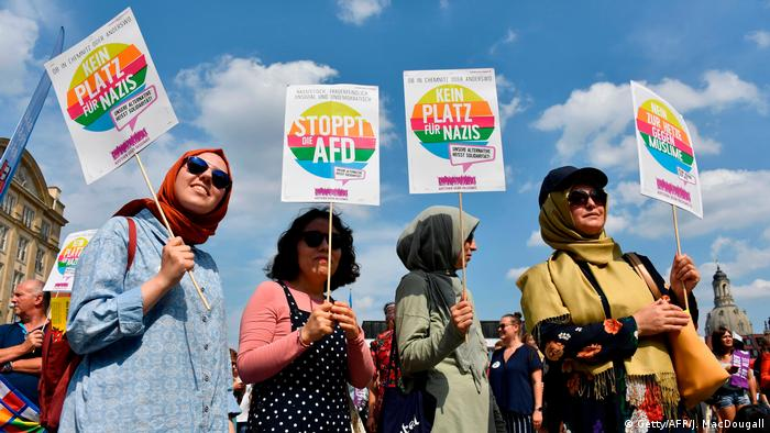 Women hold up signs at a protest aginst racism in Dresden, Germany