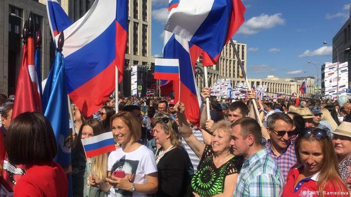 Люди на проспекте Сахарова с флагами России