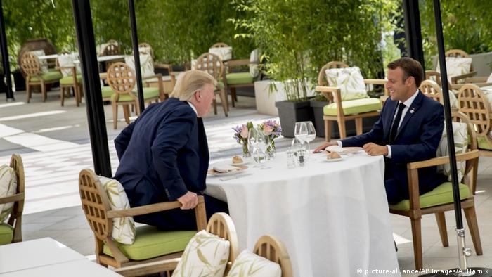 Presidente francês Emmanuel Macron e Donald Trump sentado a mesa em jardim