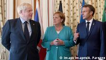 Britain's Boris Johnson, Germany's Angela Merkel and France's Emmanuel Macron strike poses at the G7 in front of flags (Imago Images/A. Parsons)
