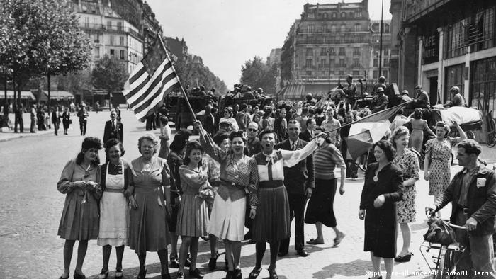 French civilians with hastily made American and French flags greet U.S. and Free French troops entering Paris, France, on August 25, 1944
