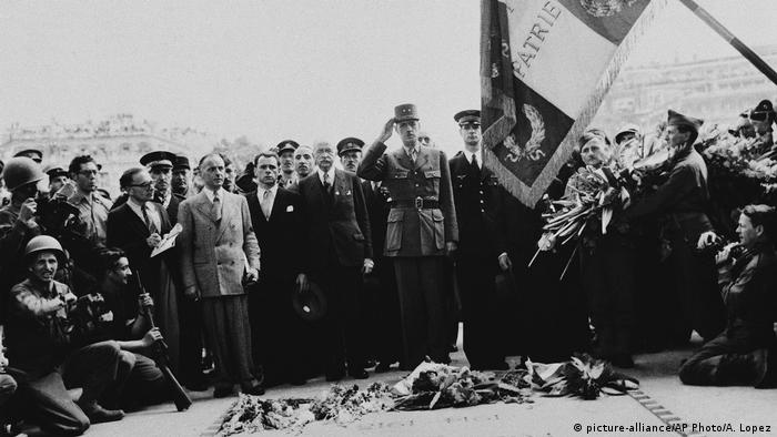 General Charles De Gaulle, center, salutes the Tricolor after placing his wreath on the Tomb of the French Unknown Soldier in Paris, France on August 28, 1944
