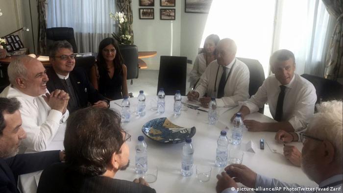 Ministro do Exterior iraniano, Javad Zarif, e presidente francês Emmanuel Macron sentados a uma mesa, com outros convidados