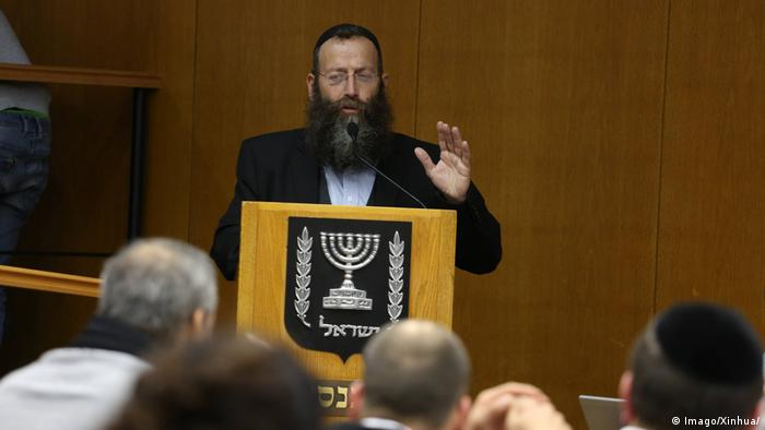 Baruch Marzel holds up his hand whiel speaking at a podium (Imago/Xinhua/)