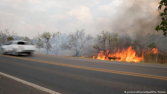 Пожар на обочине автомагистрали, по которой проезжает машина