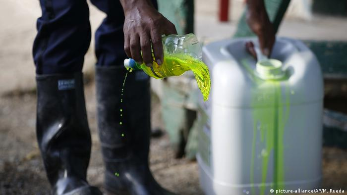 Foto simbólica de una persona con un recipiente con químicos en Colombia