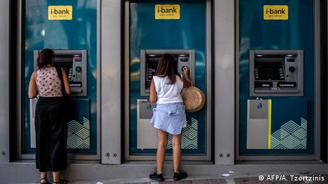 Two women stand at a bank's ATM machine (AFP/A. Tzortzinis)