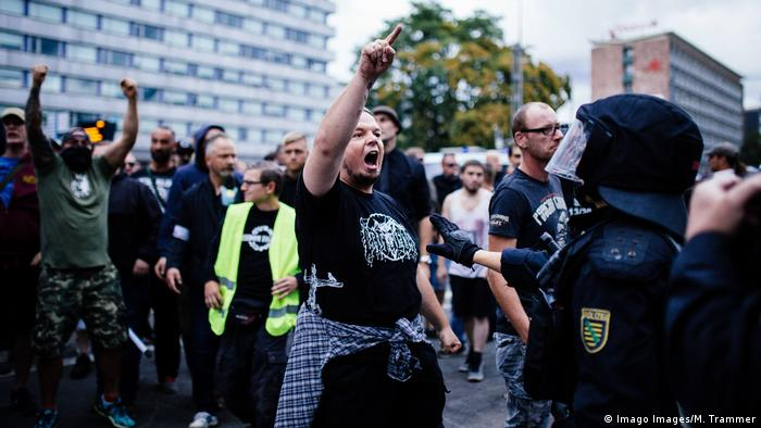 A demonstrator in Chemnitz during the 2018 far-right protests shouts at the police and raises a hand in the air (Imago Images/M. Trammer)
