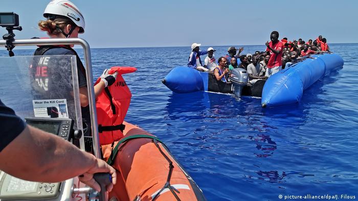 Спасатели и лодка с беженцами в Средиземном море