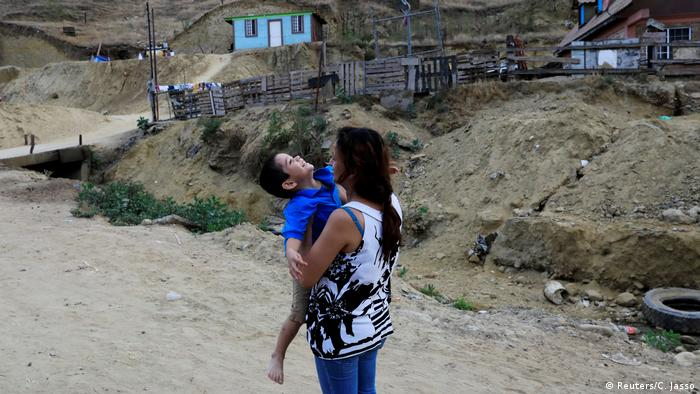 Mamá migrante abrazando a su hijo.