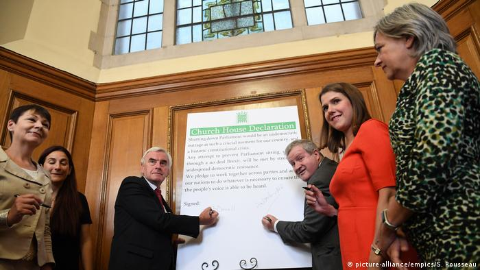 John McDonnell and Ian Blackford sign a declaration as Caroline Lucas and Luciana Berger, Jo Swinson and Liz Saville Roberts watch (picture-alliance/empics/S. Rousseau)