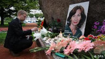 A man lights a candle in front of a portrait of Estemirova