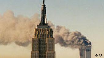 The twin towers of the World Trade Center burn behind the Empire State Buildiing in New York