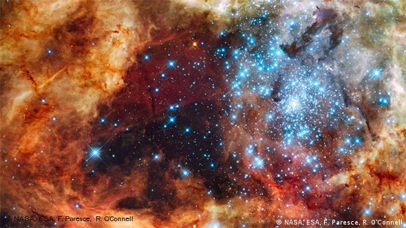 Hundreds of brilliant blue stars wreathed by warm, glowing clouds in the stellar nursery of the 30 Doradus Nebula, a turbulent star-birth region in the Large Magellanic Cloud (Photo: Hubble Space Telescope)