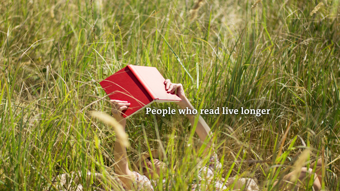 Person lying in the grass holding a book: People who read live longer