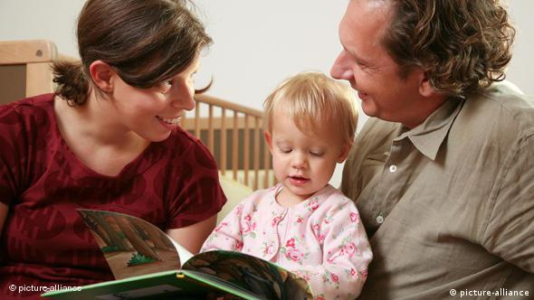 A mother and a father reading a book to their baby