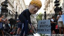 A demonstrator, wearing a mask depicting Britain's Prime Minister Boris Johnson, and a mock gravestone inscribed with the words RIP British Democracy protests outside the gates to Downing Street in central London on August 28, 2019. - British Prime Minister Boris Johnson announced Wednesday that the suspension of parliament would be extended until October 14 -- just two weeks before the UK is set to leave the EU -- enraging anti-Brexit MPs. MPs will return to London later than in recent years, giving pro-EU lawmakers less time than expected to thwart Johnson's Brexit plans before Britain is due to leave the European Union on October 31. (Photo by DANIEL LEAL-OLIVAS / AFP)