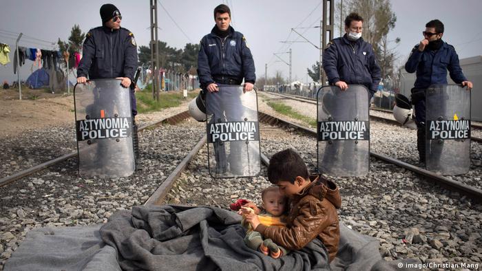 Griechenland | Kinder und Polizisten im Flüchtlingscamp Idomeni (imago/Christian Mang)