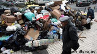 A lottery peddler passes a pile of garbage in central Athens, Greece, 11 December 2009. Sanitation workers of the Municipality of Athens have been on strike since 30 November but it is scheduled to end this evening EPA/ORESTIS PANAGIOTOU +++(c) dpa - Bildfunk+++