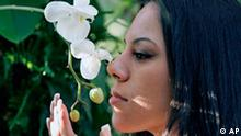 Tabath Vargas of New York City checks the scent of white orchid at the orchid show on display through April 6th at the New York Botanical Garden in New York, Sunday, Feb. 24, 2008. Some orchids are fragrant, while others smell like rotting meat or fish and still others have no scent at all. (AP Photo/Kathy Willens)