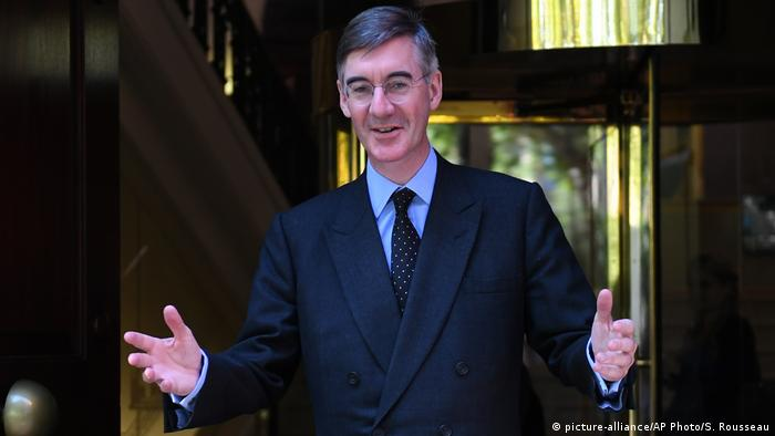 Brexit Jacob Rees-Mogg stands with his arms out and hands facing forward in a polka-dot tie