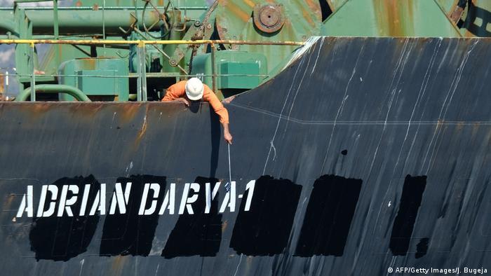 Operário debruçado no convés de navio, pinta nome no casco: Adrian Darya-1