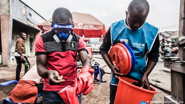 Health workers in the DRC hold containers while wearing protective masks (Getty Images/AFP/P. Tulizo)