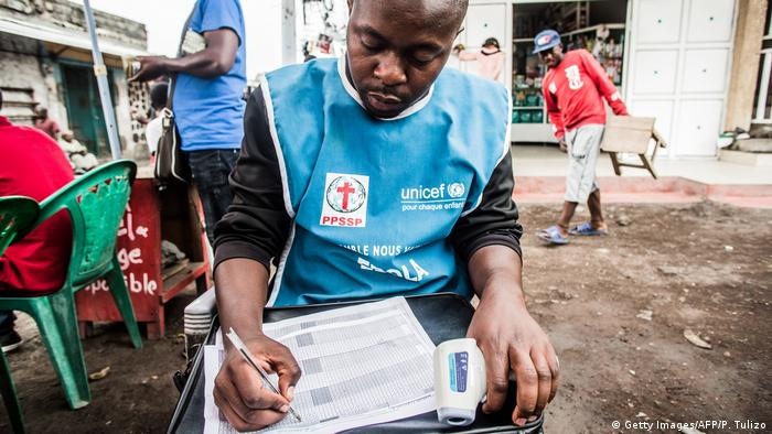 A health worker in Kongo is filling out a list on paper.