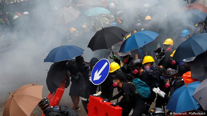 Manifestantes com guarda-chuvas e capacetes em meio a fumaça de gás lacrimogêneo