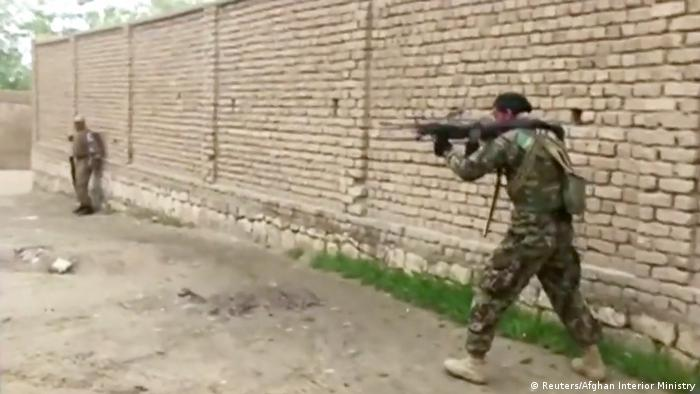 Afghan security personnel fires towards Taliban positions on the street in Kunduz
