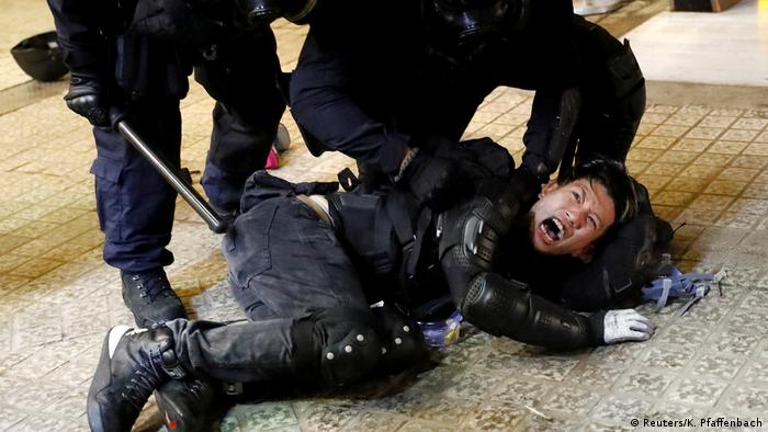 A demonstrator is detained by police officers during a protest in Hong Kong