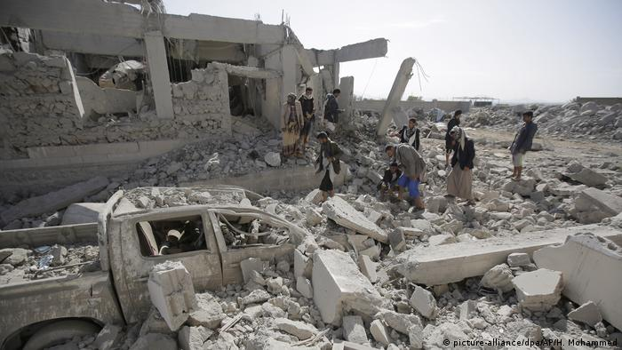 People gather around the rubble of a building hit by an airstrike in Yemen