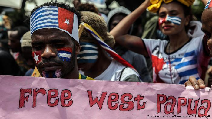 Protester with banned separatist 'Morning Star' flag with slogan: 'Free Papua'