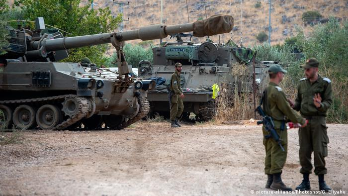 Israeli soldiers stand near artillery on the border with Lebanon