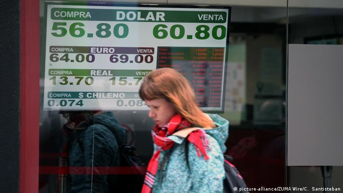 A woman walks past a currency exchange sign in Buenos Aires