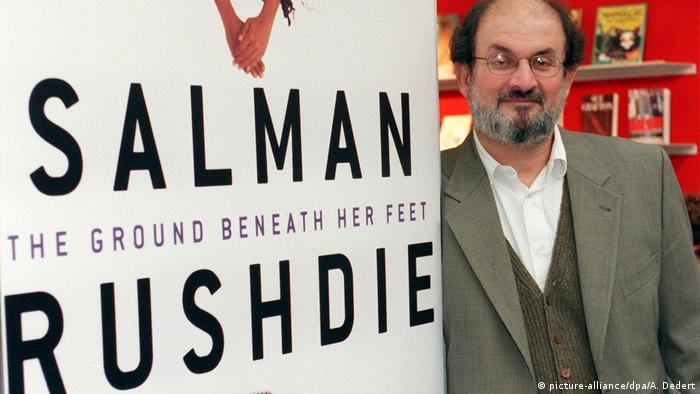 Salman Rushdie beside a panel promoting 'The Ground Beneath Her Feet' (picture-alliance/dpa/A. Dedert)
