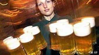 A female waiter carries handfuls of large jugs of beer