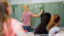 Symbolbild | junge Lehrerin schreibt an eine Schultafel im Mathematikunterricht