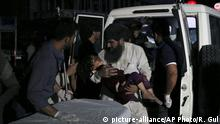 Afghan men carry an injured girl into the hospital after a large explosion in Kabul, Afghanistan, Monday, Sept. 2, 2019. Afghan officials say a large explosion in Kabul has targeted the Green Village compound, home to several international organizations and guesthouses. (AP Photo/Rahmat Gul)