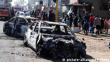 Pedestrians pass burnt out cars on the side of a street on the outskirts of Johannesburg, Monday Sept. 2, 2019. Police had earlier fired rubber bullets as they struggled to stop looters who targeted businesses as unrest broke out in several spots in and around the city. (AP Photo)