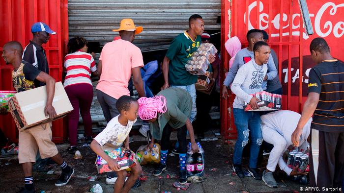 South African looters tking items from a shop