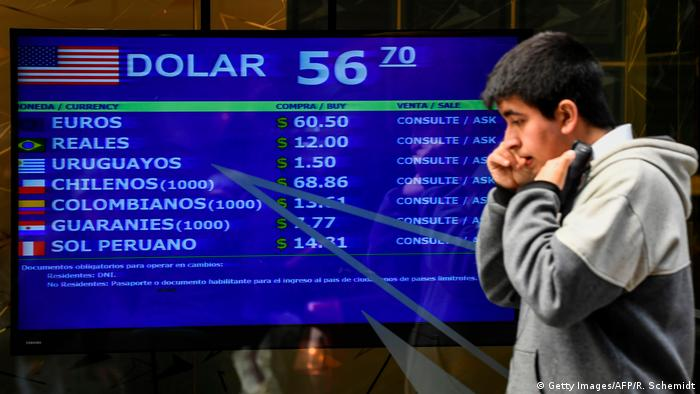 A man walks past the buy-sell board displaying currency exchange values in Buenos Aires