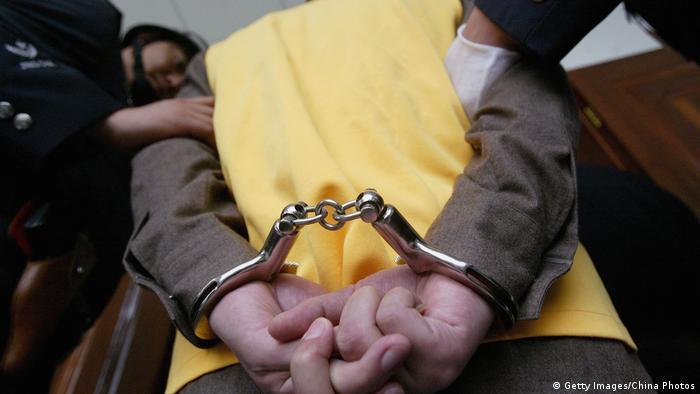 Symbolbild China Verdächtiger in Handschellen