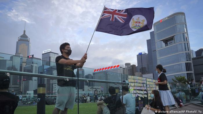 A protester waves a Hong Kong British colony flag during continuing pro-democracy demonstrations in Hong Kong's Tamar Park