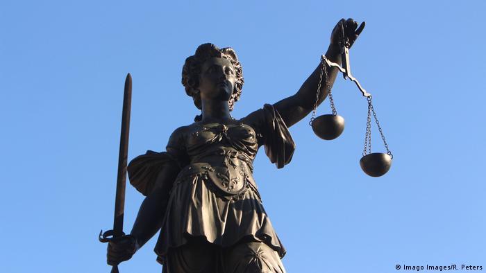 Justitia Skulptur mit Schwert und Waagschalen
