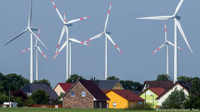 An assortment of houses standing against a backdrop of huge wind turbines